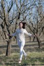 Girl in white running along old almond garden Royalty Free Stock Photo