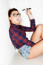 Girl with nerdy look sitting on the ground smoking and wearing glasses a checkered red shirt skimpy jeans shorts and a pony tail Royalty Free Stock Photo