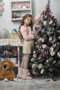 Girl next to a christmas tree decorated with rosebuds Stock Photo