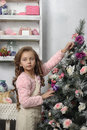 Girl next to a christmas tree decorated with rosebuds Royalty Free Stock Image