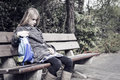 Girl with no friends little coming from school sitting lonely at a bench outdoors bullied or depressed child Royalty Free Stock Photos