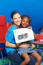 Girl and nursery teacher showing painting water color in kindergarten Royalty Free Stock Photos