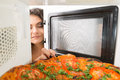 Girl open a microwave attractive Royalty Free Stock Images