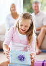 Girl opening gift box with her parents at back Stock Images
