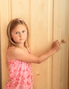 Girl opening wardrobe blond in pink t shirt wooden Royalty Free Stock Photo