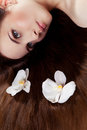 Girl with orchids in hair beautiful lying on the floor two white her long Royalty Free Stock Photography