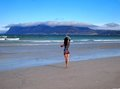 Girl in oriental clothes young beautiful woman walking on the sunrise beach cape town muizenberg atlantic ocean south africa Stock Photos