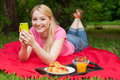Girl outdoor in the park on picnic using her cell phone blonde Royalty Free Stock Images