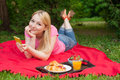 Girl outdoor in the park on picnic using her cell phone blonde Royalty Free Stock Photos