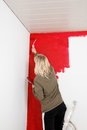 Girl with paint roller painting a room in red color Royalty Free Stock Images