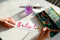 Girl painter writes with brush and paints inscription on sheet,