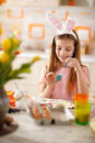 Girl painting egg in blue for Easter festivity Royalty Free Stock Photo