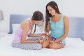 Girl painting her friends nails on bed at girls night Royalty Free Stock Photography