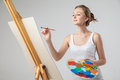 Girl paints on canvas with oil colors over white Royalty Free Stock Photo