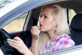 Girl paints her lips at the wheel the car Royalty Free Stock Photo