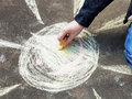 Girl paints a sun with colored chalk on asphalt outdoors Royalty Free Stock Images
