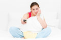 Girl in pajamas with remote control TV Royalty Free Stock Photo