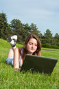 Girl in park lies on grass and work with laptop. Royalty Free Stock Photo