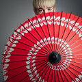 Girl peeking over red parasol a short haired her Royalty Free Stock Photos