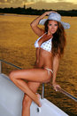 Girl with perfect figure in white bikini posing on deck of luxury yacht Royalty Free Stock Photo