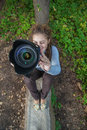 Girl photographer curly photographs against summer nature Royalty Free Stock Photo