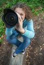 Girl photographer curly photographs against summer nature Royalty Free Stock Image