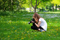Girl photographing flowers in meadow crouched holding camera with telephoto lens Stock Photo