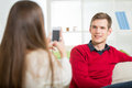 Girl photographs her boyfriend in the living room selective focus Royalty Free Stock Image