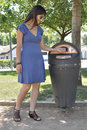 Girl picking up dog excrement bag in park Stock Photos