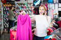 Girl picking a warm jacket young in the shop while talking to the phone Royalty Free Stock Photo