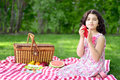 Girl at picnic using red napkin in the garden Stock Photos