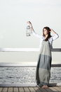 Girl on pier with kerosene lamp full length young woman a oil concept carrying light daylight Royalty Free Stock Image