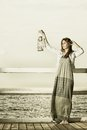 Girl on pier with kerosene lamp sepia photo full length young woman a oil concept carrying light daylight Stock Photography