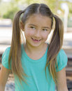 Girl with pig tails a long brown hair in and brown eyes who just lost her two front teeth smiles as she stands and looks sideways Royalty Free Stock Photography