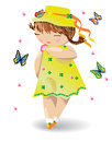 A girl with pigtails in a yellow dress and a hat with butterflies on her hat, a flower in her hand Royalty Free Stock Photo