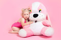 Girl in a pink bathing suit hugging a stuffed toy Stock Photos