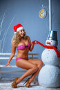 Girl in a pink bikini with snowman сhristmas mood Royalty Free Stock Photo