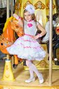 Girl in pink dress little beautiful and white leaning on a carousel pony Stock Image