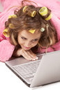 Girl in pink dressing gown lying with laptop Royalty Free Stock Image