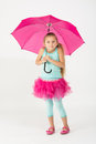 A girl in a pink skirt is chilly with umbrella Stock Photos