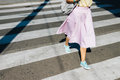 Girl in a pink skirt and sneakers crossing the road in the summe Royalty Free Stock Photo