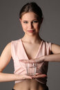 Girl in pink top holding glass of water. Close up. Gray background Royalty Free Stock Photo