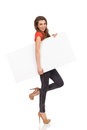 Girl with placard under the arm smiling standing on one leg and holding blank holding her full length studio shot isolated on Royalty Free Stock Images