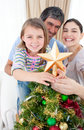 Girl placing a Christmas star on the top of a tree Stock Image