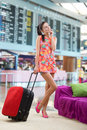 Girl planning her travel abroad pretty against a background of a departure board Royalty Free Stock Image