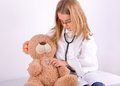 Girl play doctor with her teddy bear dressed as a treated his Stock Image