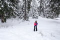 Girl play snowballs in winter snow covered forest cute blond the color pink ski suit and black hat on the background a lot Royalty Free Stock Photo