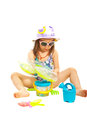 Girl playing with beach toys sitting and isolated on white background Stock Photo