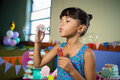 Girl playing with bubble wand during birthday party Royalty Free Stock Photo