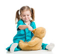 Girl playing doctor and spoon feeding teddy bear ov Royalty Free Stock Photo